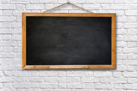 hanging on: Empty black board on white brick wall texture background Stock Photo
