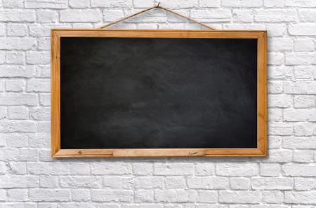 pizarra: Tablero negro vac�o en la pared de ladrillo blanco textura de fondo