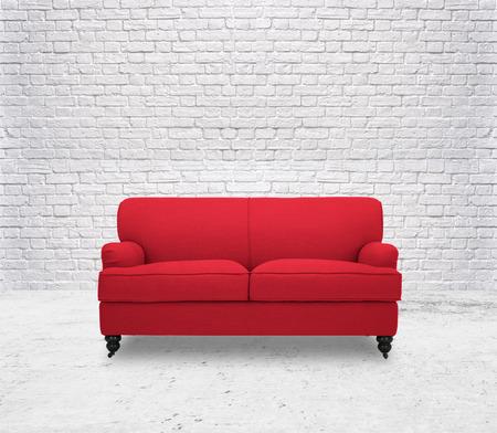 白い部屋のレンガの壁でモダンな赤いソファ
