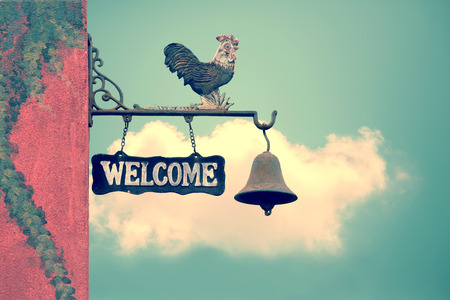 retro: Classic Door Bell with silhouette  of  chicken, vintage welcome label  on blue sky with cloud