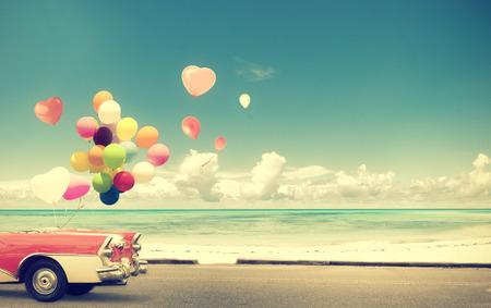 Coche de la vendimia con el globo del corazón en la playa azul cielo concepto de amor en la luna de miel del verano y de la boda