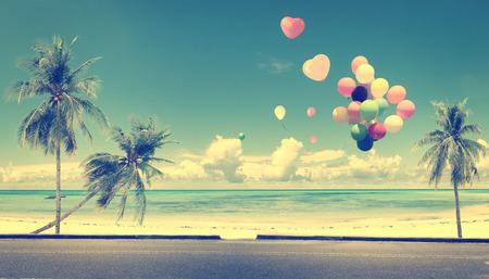 La vendimia con el globo del corazón en la playa azul cielo concepto de amor en la luna de miel del verano y de la boda
