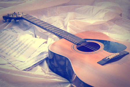 Vintage acoustic Guitar and musical notes on paper photo