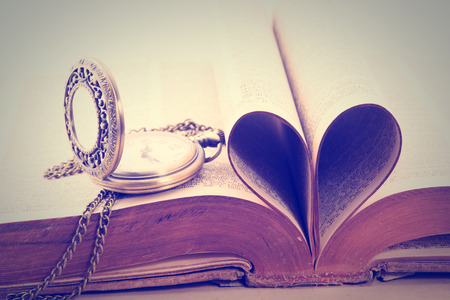 Vintage  antique pocket watch and heart of the book  pages