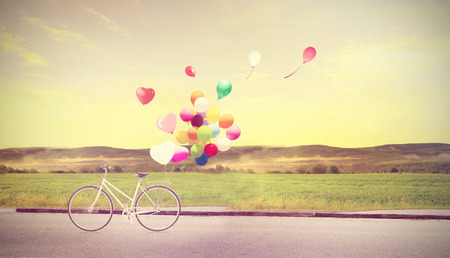 at ease: bicycle vintage with heart balloon on beach blue sky concept of love in summer and wedding Stock Photo