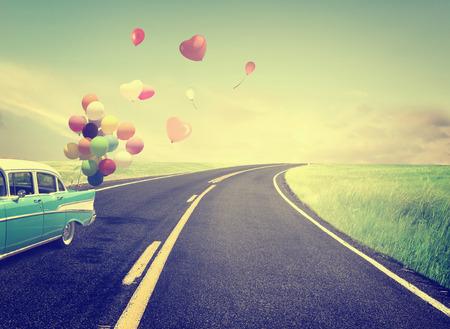 Vintage Auto met hart ballon concept van de liefde in de zomer en de bruiloft huwelijksreis Stockfoto
