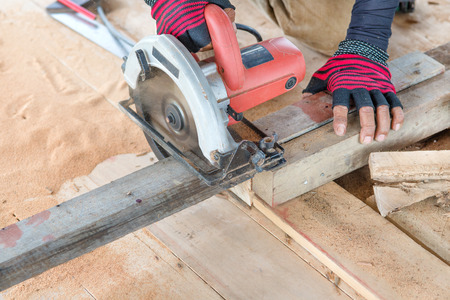Man carpenter  cutting wood with electric saw, for  Home Building photo