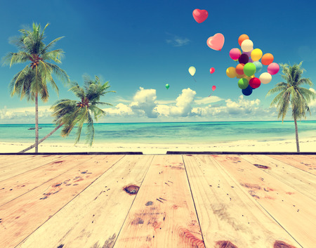 Vintage wooden floor with heart balloon on beach blue sky concept of love in summer and wedding honeymoon 版權商用圖片