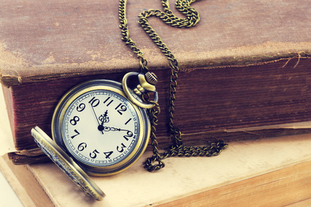 hands in  pockets: Vintage grunge still life with antique pocket watch, and old book
