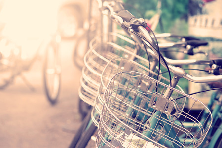 summer: Detail of a Vintage Bicycle Travel Resting in the city Street with sunlight in morning (vintage color toned image)