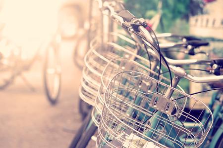 verano: Detalle de una bicicleta del vintage del viaje de descanso en la calle de la ciudad con la luz del sol en la ma�ana (imagen a color entonado de la vendimia)
