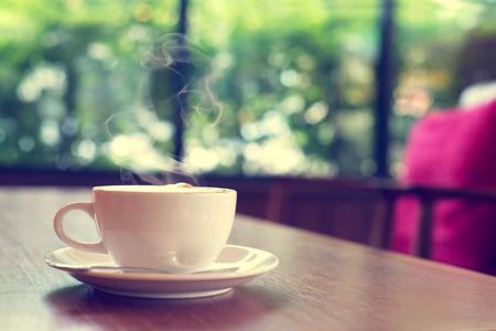 Taza de café sobre la mesa en el café de la mañana la luz, vintage o retro color tonificada