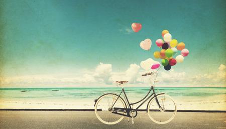 Tarjeta de papel de la bicicleta de la vendimia con el globo del corazón en la playa azul cielo concepto de amor en la luna de miel del verano y de la boda