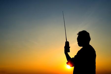 radio activity: silhouette man with radio communication, sunset on blue sky background