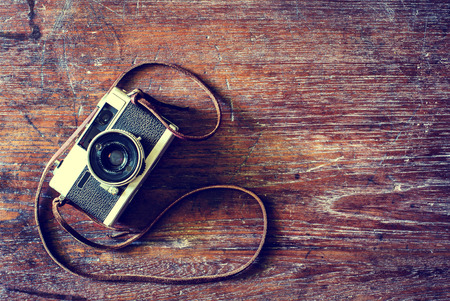 Retro camera on wood table background, vintage color tone photo