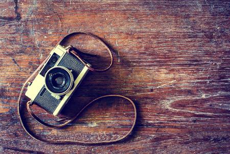 camera: Retro camera on wood table background, vintage color tone