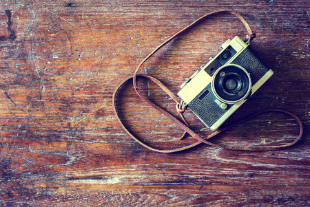 vintage backgrounds: Retro camera on wood table background, vintage color tone