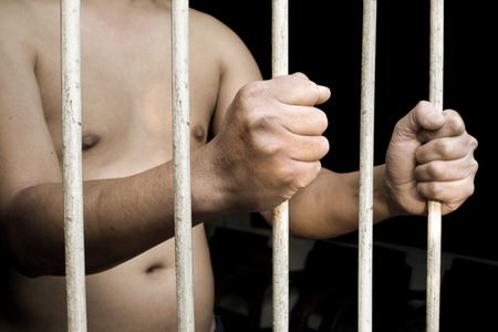 Hands of man prisoner gripping in and out on rusty prison bars Stock Photo