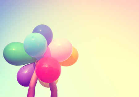 spaciousness: Girl hand holding multi colored balloons. Stock Photo