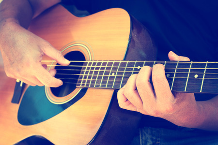 Details of performer man hands playing acoustic guitar musical, vintage retro photo