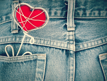 Blue jeans texture pocket and red heart, love and valentine concept (vintage color tone) photo