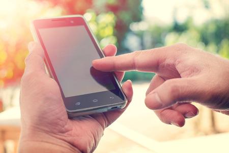 모바일 스마트 폰이 야외 사용하여 사람, 자연 배경의 닫습니다. (빈티지 색조)