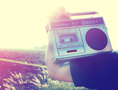 retro styled: Man hand holding vintage radio on nature background