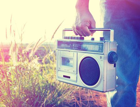 Man main tenant la radio vintage sur la nature de fond Banque d'images