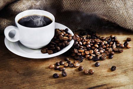 granos de cafe: Taza de caf� caliente y granos de caf� asadas en una mesa de madera. Fondo oscuro