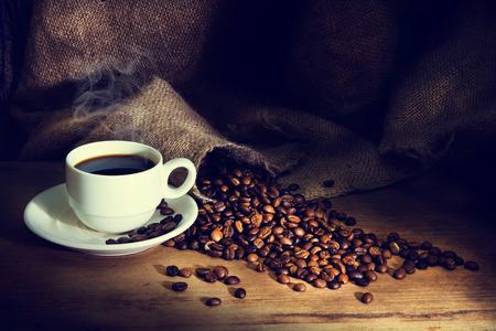 filiżanka kawy: Filiżanka kawy i ziarna kawy na drewnianym stole i worek tle, vintage odcienia koloru