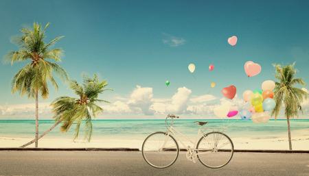 luna de miel: vendimia de la bicicleta con el globo del coraz�n en la playa azul cielo concepto de amor en la luna de miel del verano y de la boda Foto de archivo