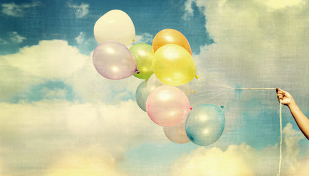 spaciousness: Girl hand holding multi colored balloons done with a retro vintage, concept of happy birth day in summer and wedding honeymoon party (Vintage color tone) Stock Photo
