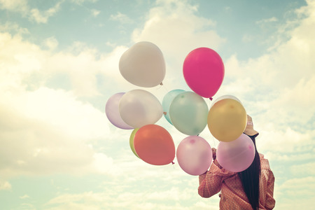 Vintage photo of  Happy young gilr  holding colorful balloons and flying on clouds sky background.