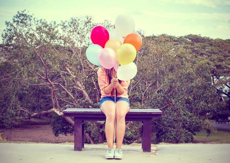 Foto del vintage de Feliz mujer joven sosteniendo globos de colores y sentado en el banco