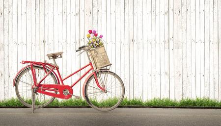 vintage fiets met boeket bloemen concept van de liefde in de zomer en bruiloft huwelijksreis, witte houten achtergrond Stockfoto