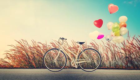 globo: vendimia de la bicicleta con el globo del coraz�n en el campo de flores silvestres y el cielo azul concepto de amor en la luna de miel del verano y de la boda Foto de archivo