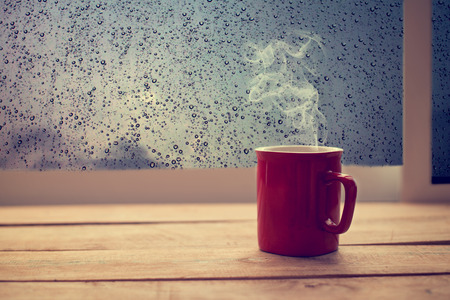 Hot coffee red cup on wood table with raindrop window, morning time