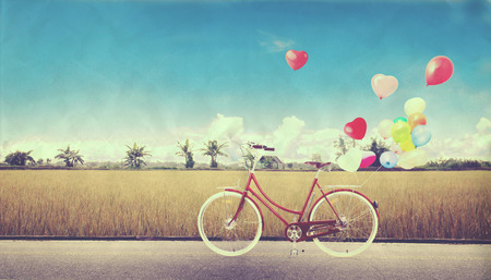 blue vintage background: bicycle vintage with heart balloon on farm field and blue sky concept of love in summer and wedding honeymoon