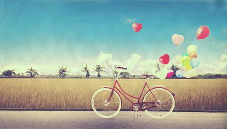 vendimia de la bicicleta con el globo del corazón en el campo agrícola y cielo azul concepto de amor en la luna de miel del verano y de la boda