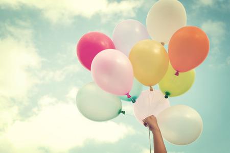 globos de cumpleaños: Mano de la muchacha que sostiene los globos multicolores hechas con un efecto retro filtro de la vendimia, el concepto de día de nacimiento feliz en el verano y la fiesta de luna de miel de la boda (el tono del color de la vendimia)