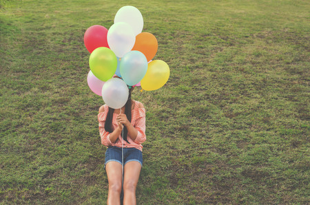 spaciousness: Vintage photo of  Happy young girl holding colorful balloons and sitting on grass field