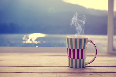 windowsill: Hot coffee cup on wood table with raindrop window, summer time