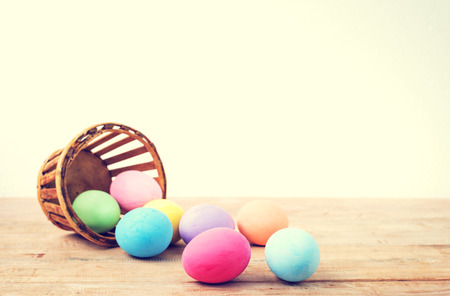 basket: Vintage colorful easter eggs on wood table empty background Stock Photo