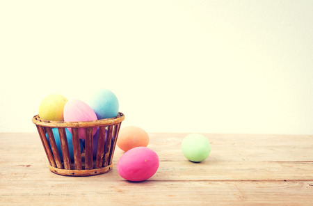 baskets: Vintage colorful easter eggs on wood table empty background Stock Photo