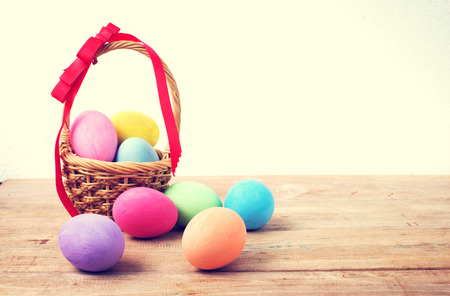Vintage colorful easter eggs in basket on wood table background