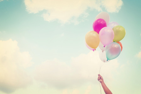 fly: Girl hand holding multicolored balloons done with a retro vintage  Stock Photo