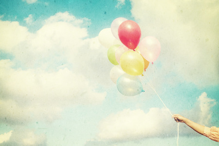 spaciousness: Girl hand holding multicolored balloons done with a retro vintage