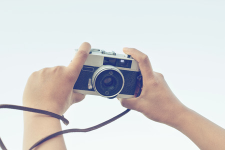 woman hand holding camera for selfie, vintage effect