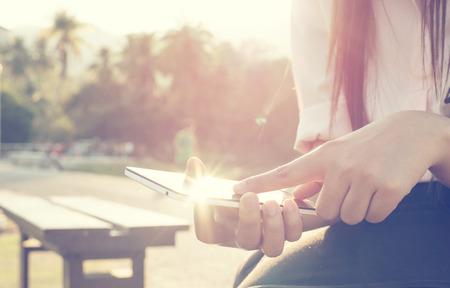 女性の屋外、モバイルのスマート フォンを使用して、自然の背景のクローズ アップ。(ヴィンテージ色のトーン)