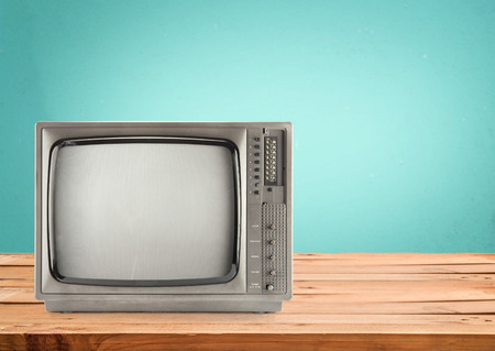 television screen: Retro Television on wood table with vintage aquamarine wall background